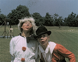A close up still image taken from TID 12269, showing two boys aged around 13 years old dressed in fancy dress clothing in a field. The boy on the left is dressed as a clown in a white suit with red pom-pom buttons and a blonde fluffy wig, and the boy on the right  is dressed in a red and white shirt style riding jacket and bowler hat. Both boys have make up on their faces with drawn in moustaches and beards. The boys pose and make humorous faces for the camera.