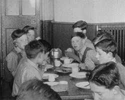 A black and white indoor still image taken from TID 12270, showing a group of boys sat around a dining table eating a meal together. The boys are dressed in their Feagan's uniform talking to each other.