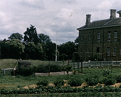 A colour ultra wide still image taken from TID 12271, showing the multi-storey exterior of the Yardley Gobion Feagan's Boys Home, with a large garden filling the foreground.