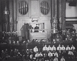 A black and white still image taken from TID 12275, showing the interior main hall stage area with organ of Central Methodist Hall, Westminster. A large group of boys and girls fill the stage in neat rows. A man sits playing the organ on the wooden plinth in the middle as a second man stands to his left. The boys and girls are dressed in their own organisation uniforms.