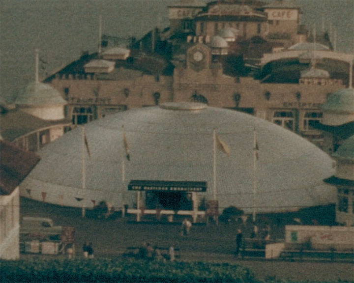 A colour still image taken from TID 12855, Showing Hastings Pier with the white domed temporary structure exhibiting the Hastings Embroidery show.