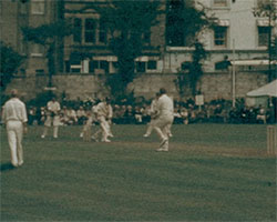 A colour still image taken from TID 12855, Showing a cricket match happening on a field. People are seen in the background watching the game.