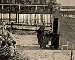 A black and white still image taken from TID 13120, showing the shore line at Bognor, where a clown is performing a juggling routine to a large group of children, that are sat on the beach in front of him. Bognor Pier can be seen in the background.