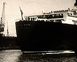 A black and white still image taken from TID 13177, showing the stern of RMS Queen Mary on the water at Southampton docks. The ships name is written on her dark coloured hull in white lettering that reads 'Queen Mary' followed by 'Liverpool' underneath. Her decks are adorned with passengers.