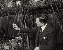 A black and white still image taken from TID 13468, showing Harry C Edmed (?) demonstrating a replication and disappearing trick using a black ball in his hand, in the garden of a family home.
