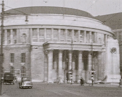 A black and white still image taken from TID 13471, showing the exterior and main entrance of Manchester Central Library on St Peter's Square, Manchester.