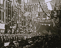 A black and white still image taken from TID 13488, showing crowds of people lining the decorated London, Ludgate Hill looking towards St Paul's Cathedral watching the King's Silver Jubilee procession.
