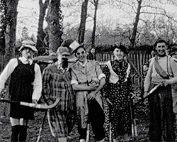 A black and white still image taken from TID 13492, showing a group photography style image of a group of men dressed in fancy dressed and women's clothing, holding Hockey sticks ready to play a match. The group are stood on a recreation ground in Weybridge, Surrey.