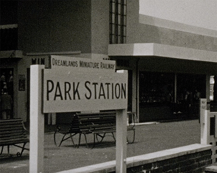 A black and white still image taken from TID 13496, showing a sign for the Dreamland Railway that reads 'Dreamland Miniature Railway, Park Station' in dark lettering on a white background. The sign is on the middle island platform in front of a light coloured art deco style building.