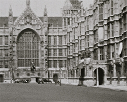 A black and still image taken from TID 13497, showing a wide view of the Palace of Westminster from the main road adjacent to Old Palace Yard.