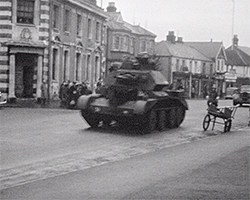 A black and white still image taken from TID 13503, showing Baker Street in Weybridge, as a military tank leads a armed forces parade along the road past shops and spectators.