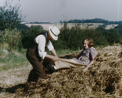 A colour still image taken from TID 13680, showing an older man playing with a child and a large haystack. The child is sat on a grain sack, which the older man is using to slide the child down the stack from the front.