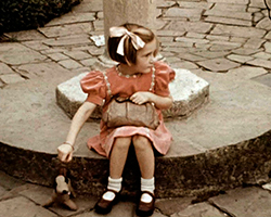 A colour still image taken from TID 13697, showing a young girl dressed in a pale pink coloured dress, sat on the base pedestal in front of a fountain with her toy stuffed dog clutching a brown leather handbag in her lap. The girl in profile, looking away from camera out of the frame.