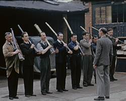 A colour still image taken from TID 13714, showing a group of workmen, members of the Local Defence Volunteers, drilling with old service rifles and broom handles in a parking area adjacent to brick buildings. The men stand in a row with their tools 'at arms'.