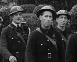 A black and white still image taken from TID 13715, showing a group of Home Guard wardens on parade dressed in full military uniforms ready for duty. The image is one of series of films from the collections of Screen Archive South East, used by MA Artist in residence David Woods. David's brief was to offer a creative response to the collection using Second World War material linking creativity, archive film and history. The work has a newly created spoken word poetry soundscape audio track.