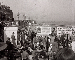 A black and white still from 'Sussex 1939', showing a very large gathering of marchers on the shingle beach in Eastbourne close to the Langham Hotel. The group have gathered to listen to speeches from Sussex Communist Party members on the promenade. Many of the marchers hold large banners and plaqards.