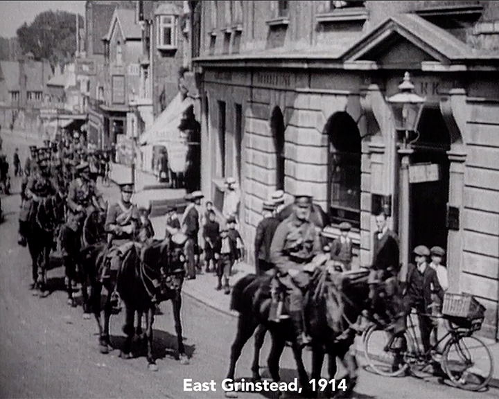 A black and white still image taken from TID 13722, showing a mounted regiment in full uniform parading through East Grinstead in 1914.