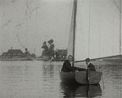 A still image taken from TID 13723.  A compilation of films edited together by Screen Archive South East. This black and white still image shows two men in a small sailing boat with full sail unfurled, on a river. Two domestic houses can be seen on the bank behind them in the distance.