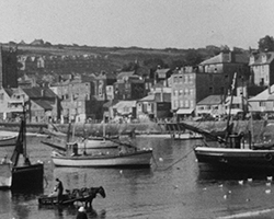A black and white still image taken from TID 13778, showing a wide landscape view of the fishing harbour at St Ives. Boats line the water in the foreground and houses stretch along the harbour wall in the background.