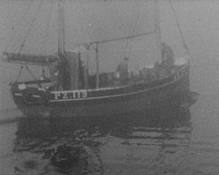 A black and white still image taken from TID 13779, showing a wide view of a shipping boat on the water surrounded by fog. The vessel bears the number P2.119 on her Starboard side toward the stern.