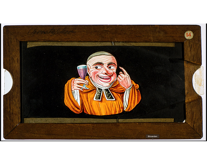 A still image taken from TID 14018, showing a close up image of a colour hand painted figure of an overweight monk with a drinkers nose, enjoying a glass of wine, beckoning us with his finger.