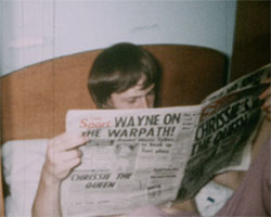 A colour still image taken from TID 1976, showing a boy reading the Sun newspaper sat in bed in his dorm room. The headline on the front page reads 'Chrissie's the Queen'.