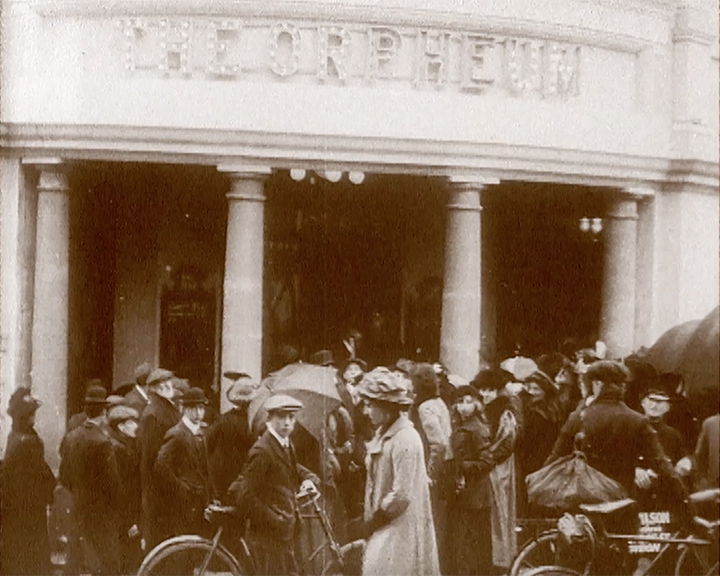 A black and white still image taken from TID 15, showing the bright white exterior facade of The Orpheum Cinema in Croydon, with a very large gathering of spectators outside on opening day.