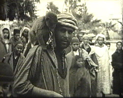 A Still from [Christmas Cruise - Trip to Africa] (ca.1935) showing a Moroccan man with a monkey