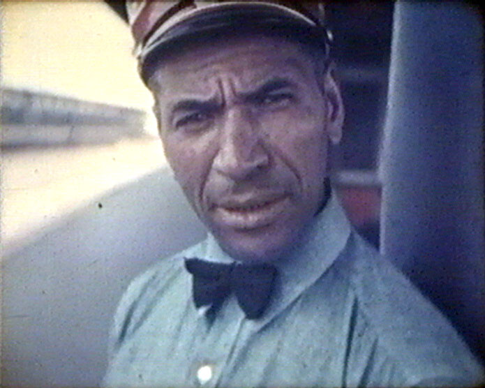 A still from 'American Visit' (1938) showing a black stationmaster