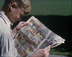 A still from [Southern Railway Orphanage - Life at the Home] (1952?) - a boy reading a comic