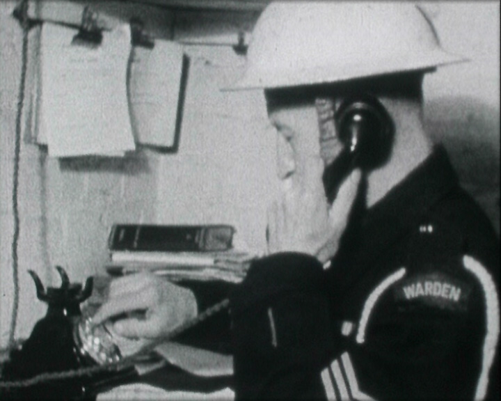 A still from 'Civilians in Uniform' (ca.1946) - an air raid warden on the telephone