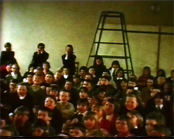 A close up colour still image from TID 1651, showing a large group of school children sat on a school hall floor with their legs crossed. A hand full of adults are stood at the back of the hall behind the children.