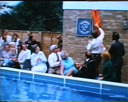 A wide colour still image from TID 1652, showing the presentation of a wall mounted plaque during the opening ceremony of the new Claygate School outdoor swimming pool.