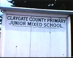 A close up colour still image from TID 1653, showing a large white painted notice board with the words 'Claygate County Primary Junior Mixed School' at the top in large black letters. The board has no notices pinned to it and is empty.