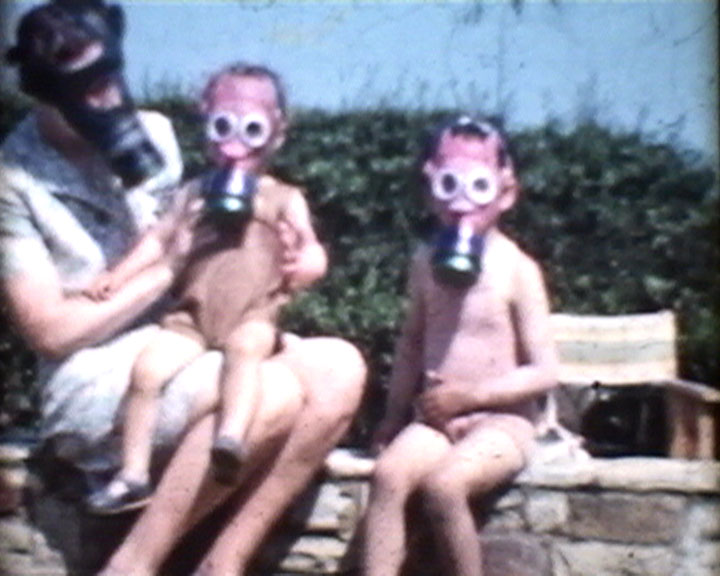 A still from [Wisborough Green] (1939-1943) - Mother and children wearing gas masks