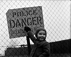 A black and white still image taken from TID 1705, showing a young girl dressed in a woollen hat, coat and mittens facing the camera whilst pointing up at at a plaquard style sign behind a chainmail fence. The sign reads 'POLICE DANGER UNEXPLODED BOMBS'.