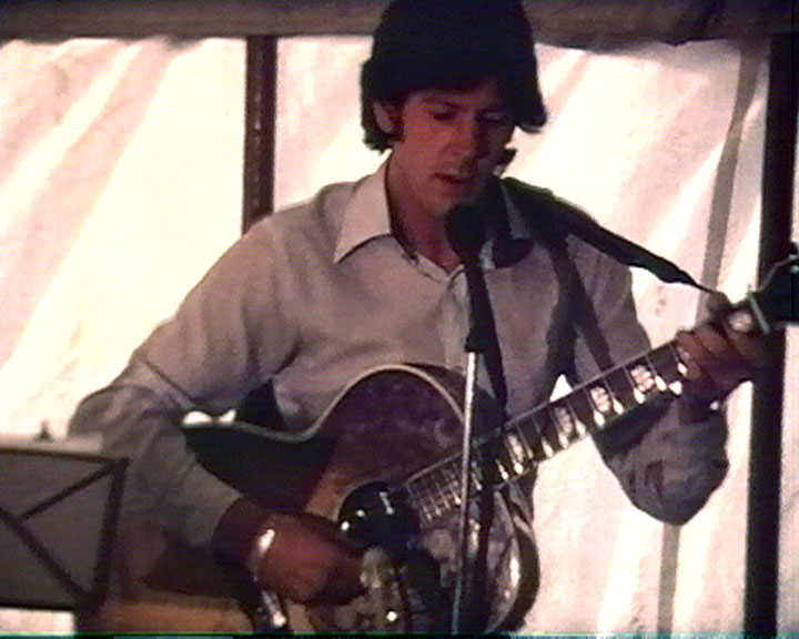 A still from '[Christian Convention, Open Day]' (1970s) - a man playing a guitar