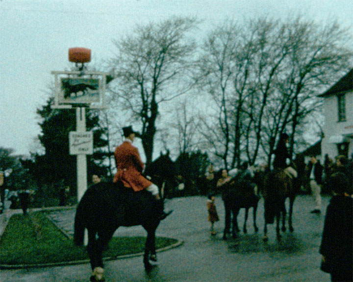 A colour still image taken from TID 233 - Horsham Scenes (1966) showing a hunting party, with riders dressed in their red riding jackets mounted on horses gathered in The Fox Public House Car Park. A group of spectators are seen in the background watching the group assemble.