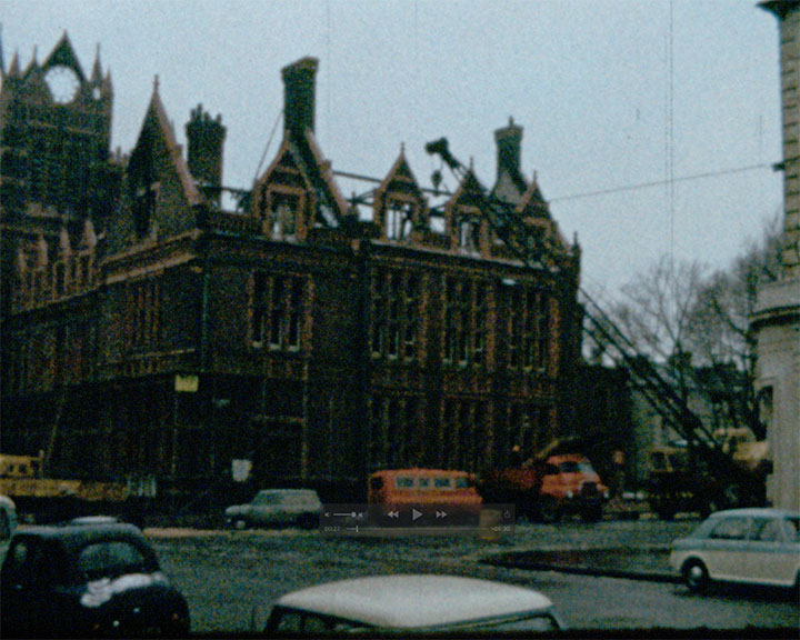 A colour still image taken from TID 233 - Horsham Scenes (1966) showing a view of Church Road, Hove, looking towards the burnt out Hove Town Hall with no roof. A crane has been errected next to the town hall and vans and lorries are parked on the road.