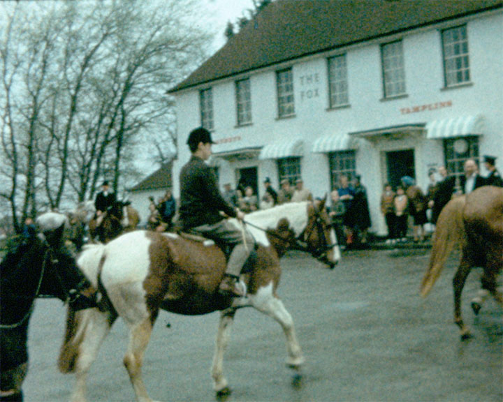 A colour still image taken from TID 233 - Horsham Scenes (1966) showing a hunting party, with riders dressed in their red riding jackets mounted on horses gathered in The Fox Public House Car Park making their way out at the start of the hunt.
