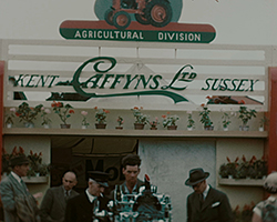 A colour still image taken from TID 2394, showing the frontage of the Caffyns LTD stand at the Kent Show. A red and green sign above the stand name reads Agricultural Division. A group of men are gathered at the entrance to the stand.