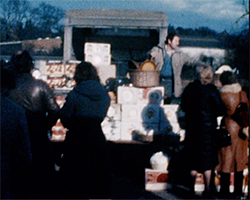 A colour still image taken from TID 3111, showing a bustling market stall. A household crockery and cutlery seller is plying his wares, as a group of visitors stand to watch his sales pitch.