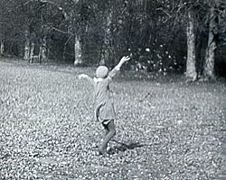 A still from 'Staley Family Domestic' (1930-1931) showing Pam Staley throwing leaves in the air