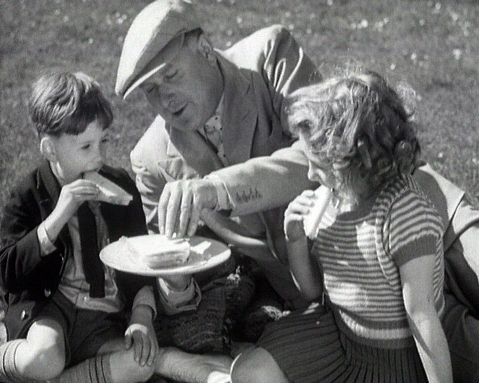 A still from 'Ancient and Modern' (1933) showing a family group eating sandwiches