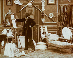 A still from 'The Artist's Nightmare' (1908) - the artist painting in his studio