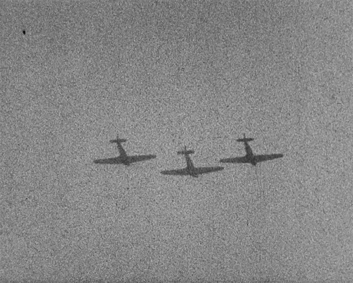 A black and white still image taken from TID 3375, showing a close up shot of the sky as three military aircraft fly overhead.