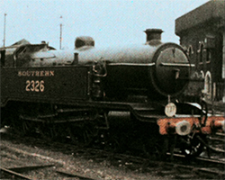 A colour still image taken from TID 3375, a Doufaycolor film showing the side profile of a Southern steam locomotive with the number '2326' marked on the side, located in the sidings close to Brighton station.