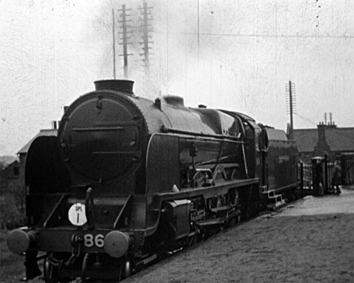 A black and white still image taken from TID 3375, showing the front and side profile of a steam SPL I (Sir Martin Frobisher) locomotive at stand, at a platform.