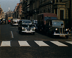 A colour still image taken from TID 3375, showing a busy London street filled with cars and commercial vehicles, passing through a pedestrian Zebra crossing.