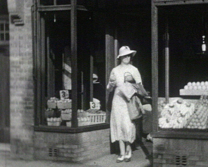 A still from [Sussex and Hampshire Scenes] (1930s) showing a woman shopping
